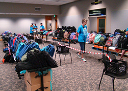Donated backpacks and school supplies stacked up at a previous Back to School Bash.